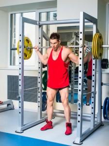 Mann Macht Kniebeugen mit Schwerem Gewicht mit Sicherung